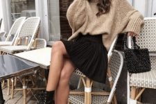 an oversized tan sweater, a black pleated mini, black combat boots and a beaded bag is amazing and chic