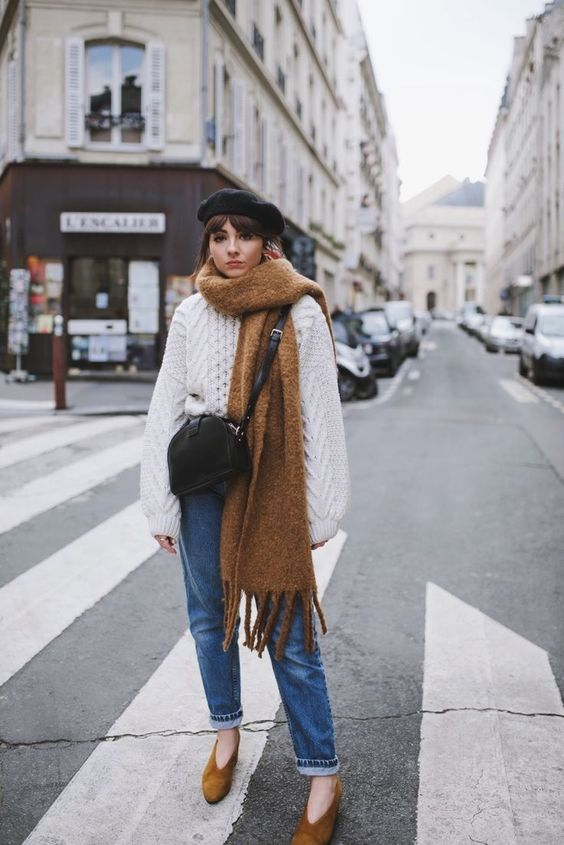 an oversized white braided sweater, blue mom jeans, mustard suede shoes, a brown scarf, a black bag and beret