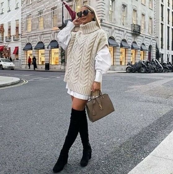 an oversized white shirt, an ivory sweater, a tan bag and black tall suede boots for a feminine look