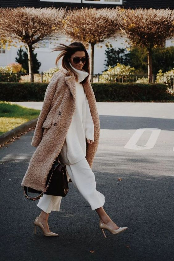 an oversized white sweater, white cropped pants, tan shoes, a brown fuzzy coat and a large black bag for work