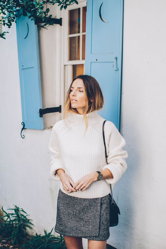 an oversized white sweater with a turtleneck, a grey wrap tweed mini skirt, a black crossbody bag