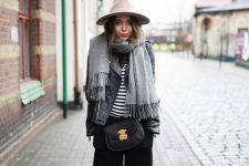 black culottes, boots, a striped top, a black leather jacket, a grey oversized scarf, a black crossbody bag and a neutral hat