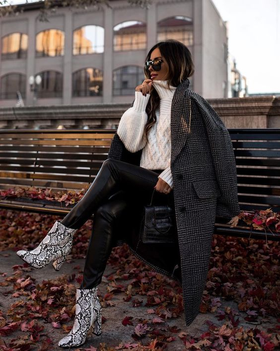 black leather leggings, an oversized white braided sweater, snakeskin booties, a grey plaid coat and a black bag