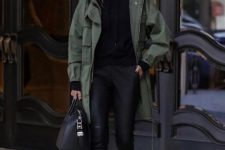 black leather leggings, black booties, a black hoodie, a green parka and a black bag