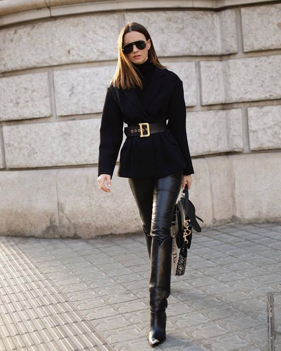 black leather leggings, wide tall boots, an oversized tuterleneck sweater with a wide belt and a black bag