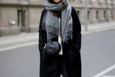 black skinnies, black Chelsea boots, a white sweater, a black coat, a crossbody bag and an oversized black scarf
