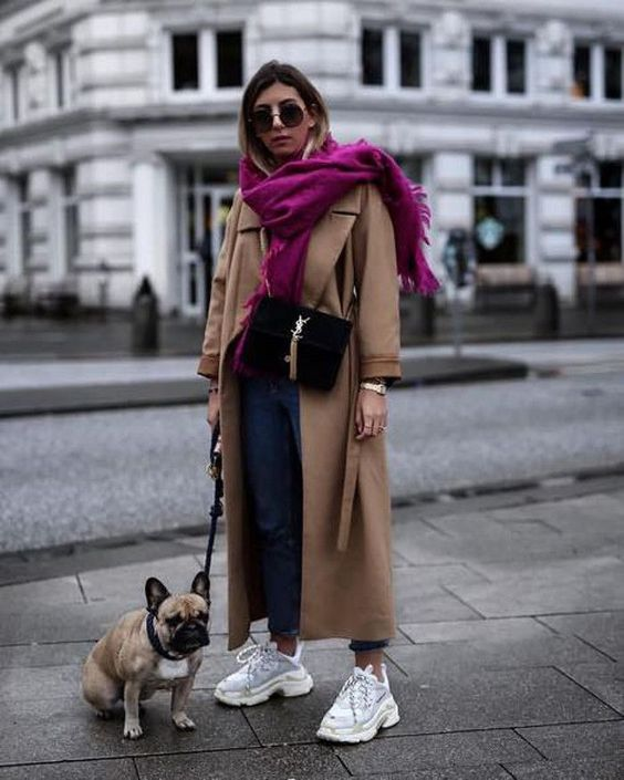 blue jeans, neutral trainers, a tan coat, a black bag and a bold fuchsia accent scarf to make a statement