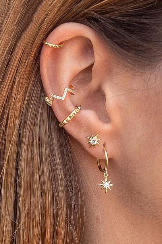 bold ear styling with embellished and spiked cuffs, an embellished stud and a gold hoop earring with a star