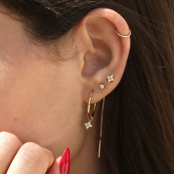 embellished studs, a tiny hoop earring in helix and a gold hoop earring with an embellished pendant star