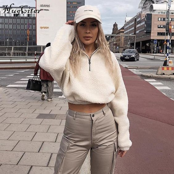 grey cargo pants, a white fuzzy zip sweater, a white cap for a sporty and chic look