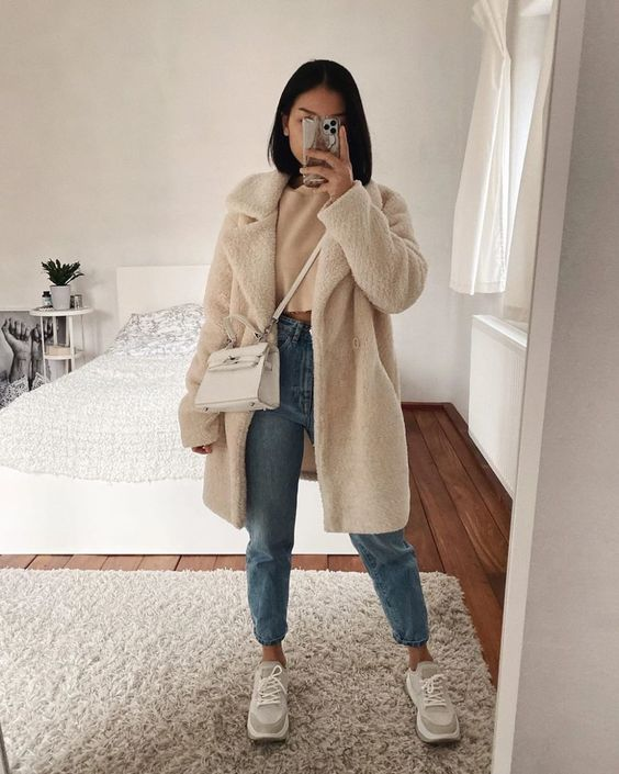 grey trainers, light blue jeans, a cropped tan sweater, a creamy faux fur coat and a creamy bag