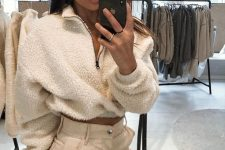 tan high waisted pants and a white fuzzy zip sweater that is cropped for a sexy feel