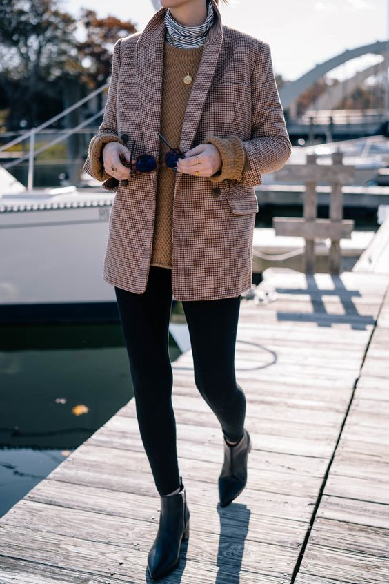 a layering look with a striped turtleneck, a tan sweater over it and a tweed blazer, leggings and booties will keep you warm