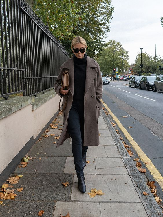a woolen turtleneck sweater, a woolen taupe coat, black jeans, booties and a tan bag for winter