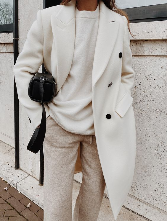 a refined outfit with neutral pants, a white woolen top, a white woolen coat and a small black bag