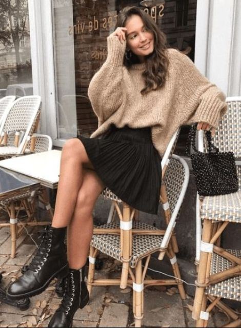 an oversized tan woolen sweater, a black pleated mini skirt, black boots and a black beaded bag
