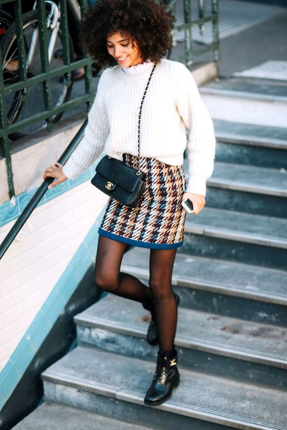 a white turtleneck sweater, a printed tweed mini skirt, black tights, black boots and a black bag