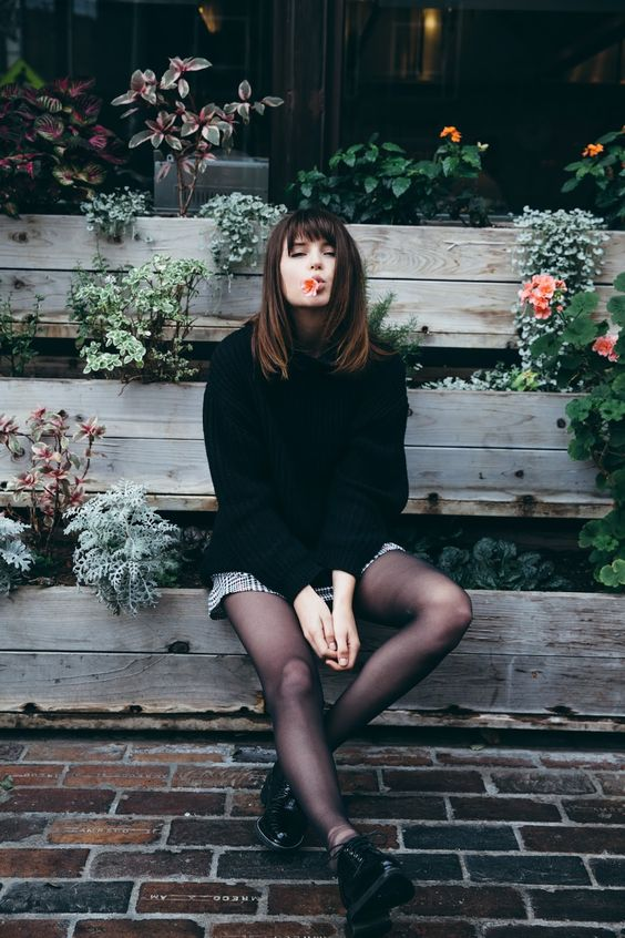 a black oversized sweater, a plaid mini skirt, tights and black platform shoes for winter