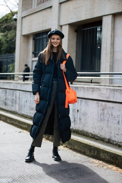 With black beret, orange bag, black shirt and gray high-waisted cropped trousers