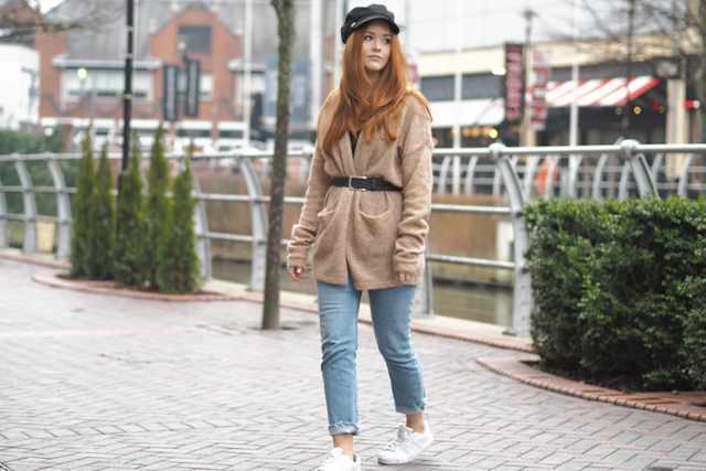 With black cap, cuffed jeans, black shirt and white sneakers