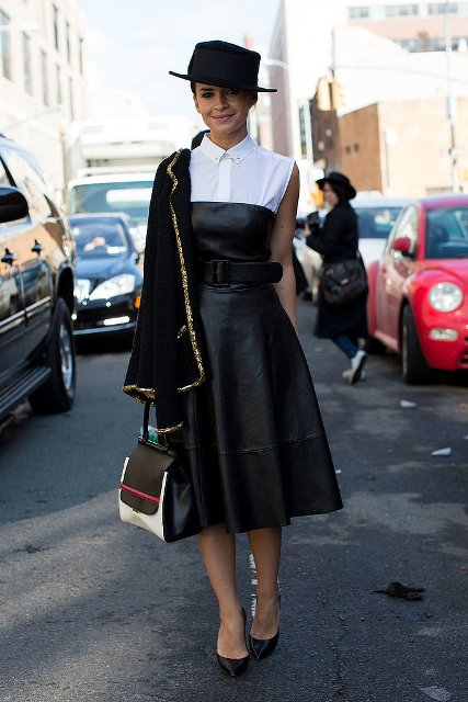 With black hat, white sleeveless blouse, black pumps, three colored bag and black and golden blazer