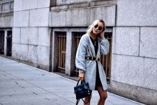 With black mini dress and navy blue bag