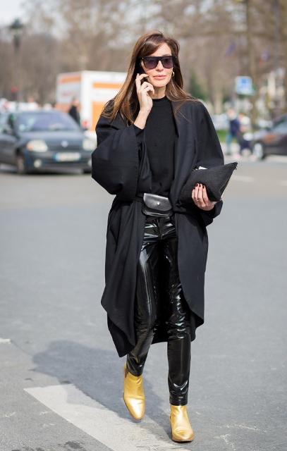 With black shirt, black leather pants, clutch and black cardigan