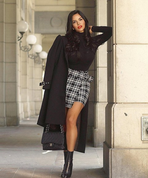 With black turtleneck, black coat, chain strap bag and mid calf boots