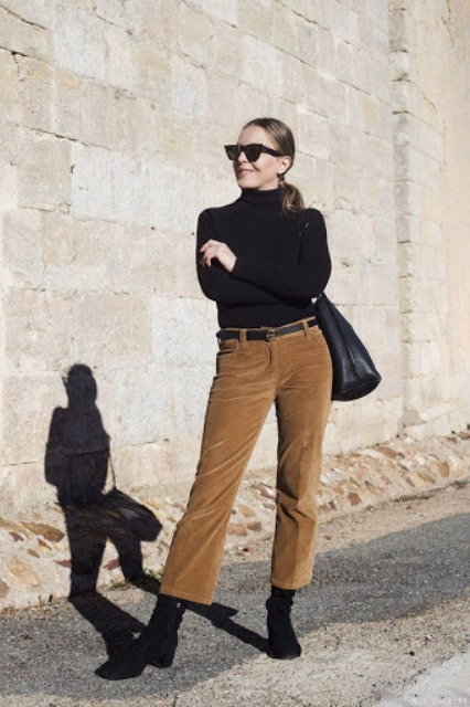 With black turtleneck, black tote bag and black suede boots