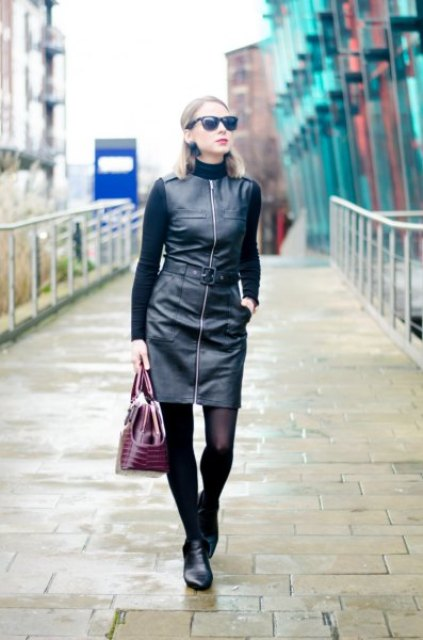 With black turtleneck, purple bag and black ankle boots