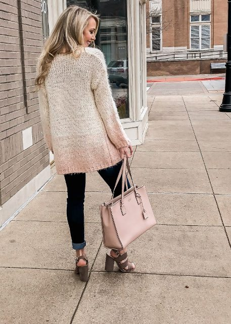 With cuffed jeans, pale pink bag and high heels