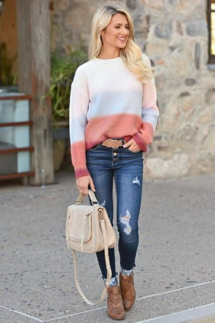 With distressed jeans, beige bag and brown boots