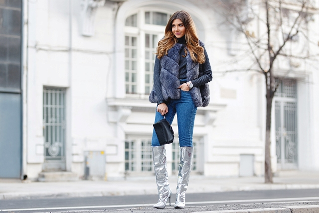 With gray sweater, fur vest, skinny jeans and black bag