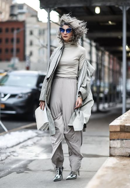 With gray turtleneck, gray loose pants, white clutch and gray coat
