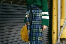 With green and white sweater, green belt, yellow fur bag and flat shoes