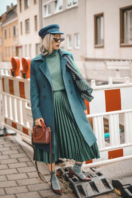 With green cap, green midi coat, pleated midi skirt, brown bag and leather shoes