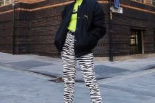 With green shirt, black bomber jacket and zebra printed pants
