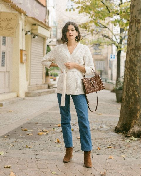 With loose jeans, brown bag and brown suede boots