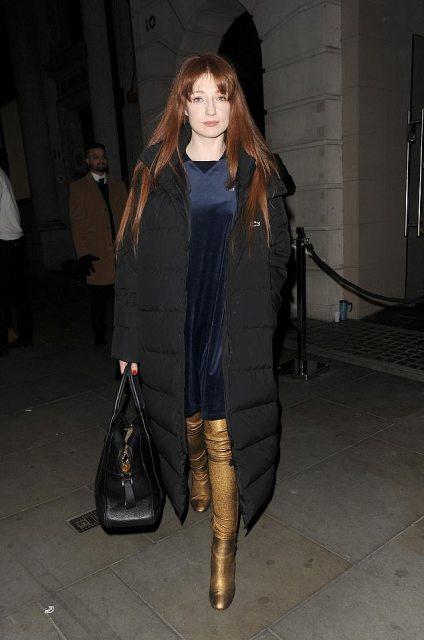 With navy blue velvet dress, black puffer coat and black bag