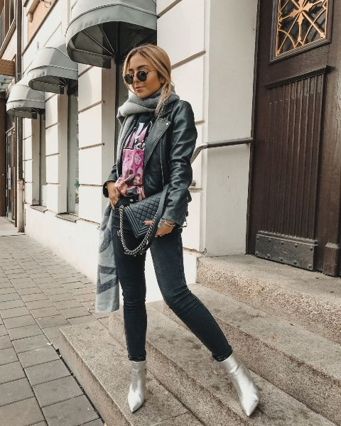 With t-shirt, black leather jacket, dark colored jeans, black bag and gray scarf
