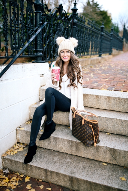 With white cardigan, white top, skinny pants, printed tote bag and black suede boots