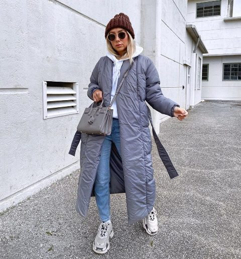 With white hoodie, brown hat, gray bag, jeans and light gray sneakers