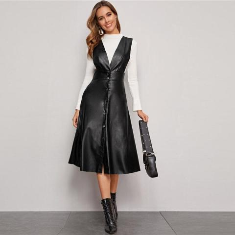 With white long sleeved shirt, black leather bag and black lace up mid calf boots
