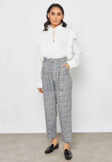 With white ruffled blouse and black leather flat shoes