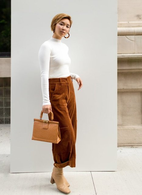 With white shirt, brown leather bag and beige leather boots