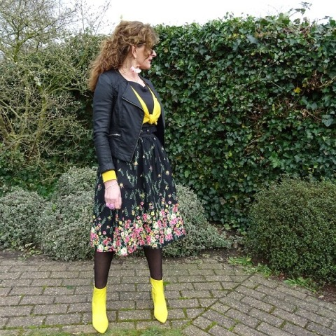 With yellow and black shirt, floral skirt and black jacket