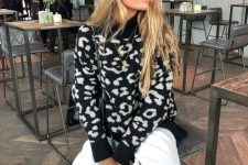 a black and white leopard print sweater, white pants and black combat boots for a monochromatic winter look