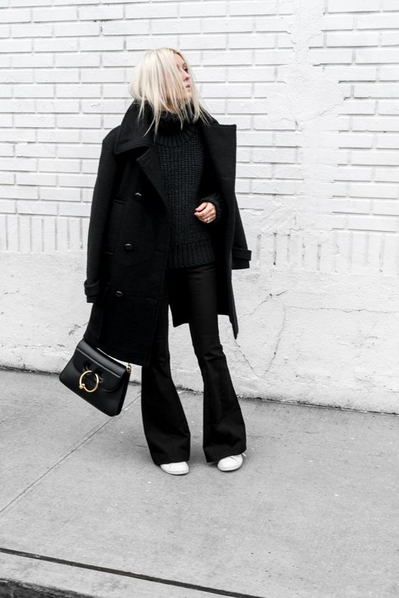 a black and white outfit with a black turtleneck chunky sweater, black flare jeans, white sneakers, a black coat and a bag