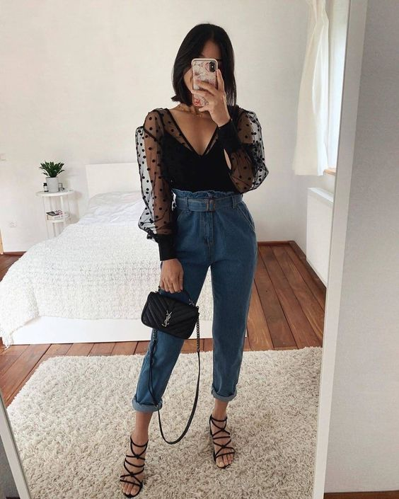 a black polka dot V-neckline blouse with puff sleeves, blue jeans, strappy heels and a black bag