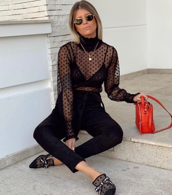a black sheer top over a black bra, black pants, polka dot mules with bows and a red bag